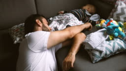 Father and son sleeping on the sofa