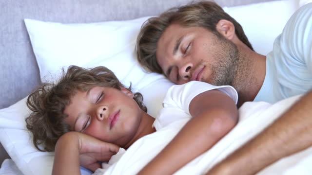 father and son sleeping together - 横向きに寝る点の映像素材/bロール