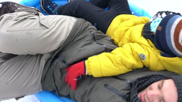father and son slide on snow with inflatable pool - 4k vertical video - 6 7 years stock videos & royalty-free footage