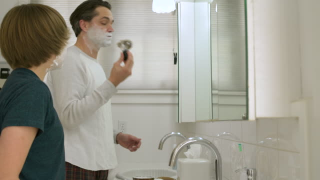vidéos et rushes de father and son smearing shaving foam on their faces - se raser