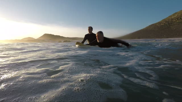 father and son son surfing together - wassersport stock-videos und b-roll-filmmaterial
