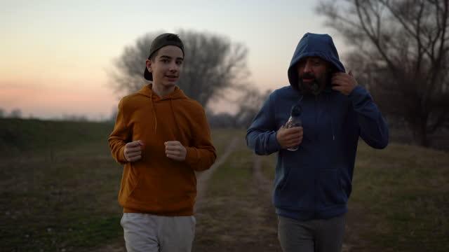 vídeos y material grabado en eventos de stock de padre e hijo pasando el día de fin de semana corriendo en la naturaleza - familia con un hijo