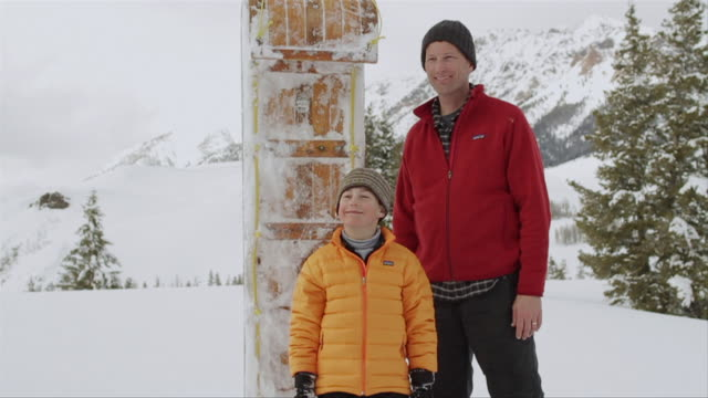 ms father and son standing aside family with toboggan / sun valley, idaho, united states - mitten stock videos and b-roll footage