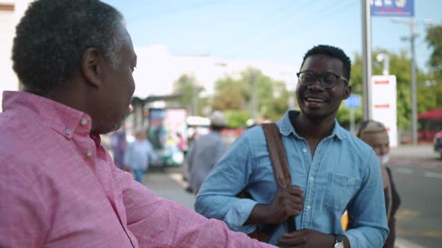 vidéos et rushes de père et fils debout près de la gare routière et parlant - son