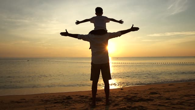 Father and Son standing on the beach at sunrise, They spend quality family time together. Shooting with slow-motion camera.