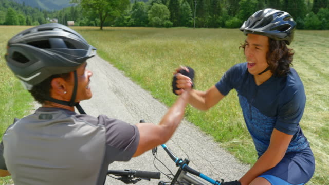 cs father and son starting their mountain bike trip up a beautiful sunny mountain valley - sports helmet stock videos & royalty-free footage