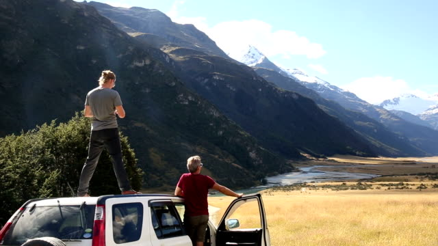 Father and son stop on 4x4 road to admire the mountain view