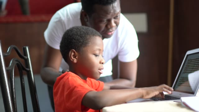 father and son studying with laptop on a online class at home - genderblend stock videos & royalty-free footage