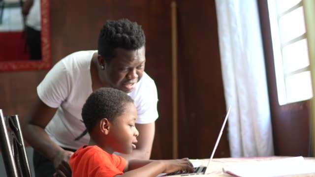 father and son studying with laptop on a online class at home - son stock videos & royalty-free footage