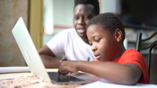 father and son studying with laptop on a online class at home - child stock videos & royalty-free footage