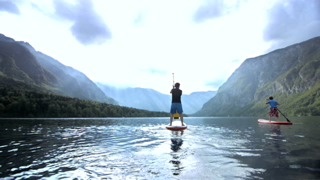 stockvideo's en b-roll-footage met father and son suping on the lake - peddel