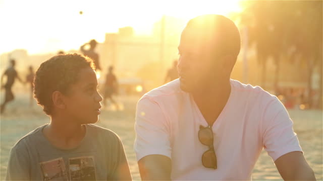 vídeos de stock, filmes e b-roll de father and son talk on sunny brazilian beach - perguntando