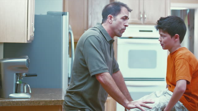 vidéos et rushes de ms father and son (12-13) talking in kitchen / renton, washington, usa  - homme soumis