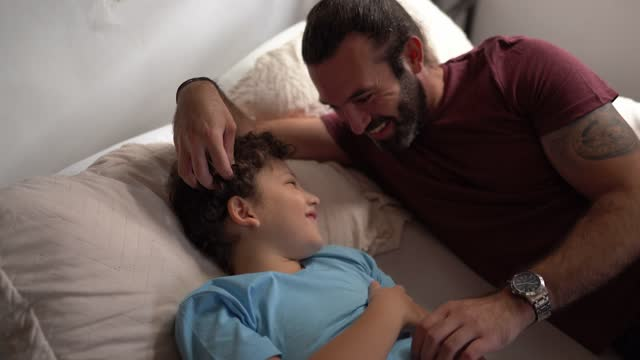 father and son together talking in bed at home - genderblend stock videos & royalty-free footage