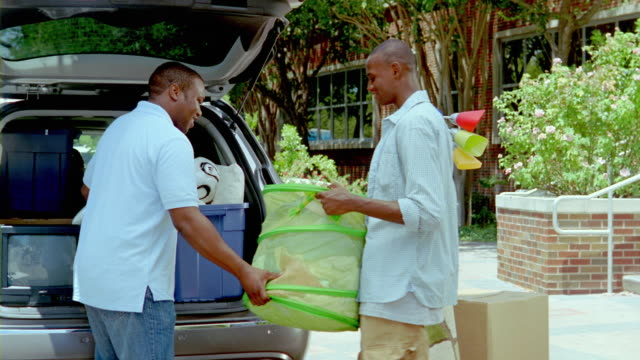 ms, father and son unloading belongings from car trunk outside college dorm building, san antonio, texas, usa - adult offspring stock videos & royalty-free footage