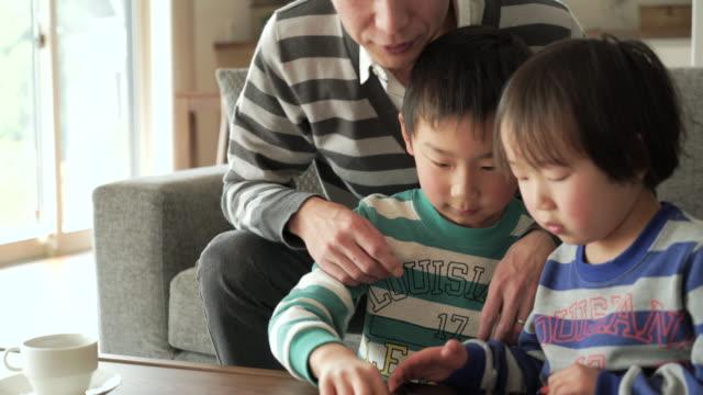 Vader en zoon met behulp van een digitaal tablet thuis