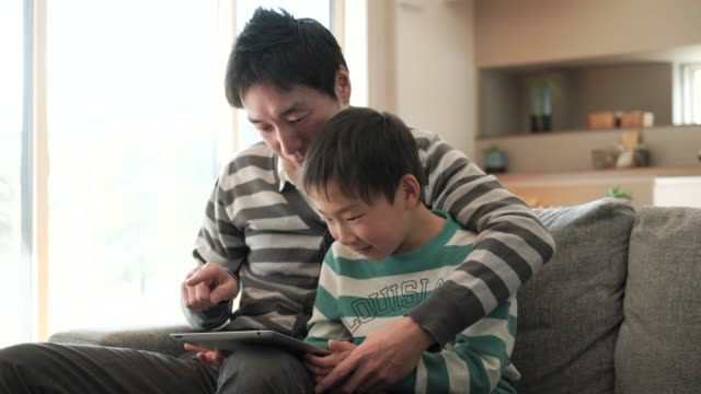 father and son using a digital tablet at home - genderblend stock videos & royalty-free footage
