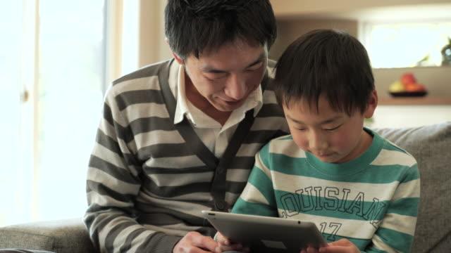 stockvideo's en b-roll-footage met vader en zoon met behulp van een digitaal tablet thuis - tablet pc