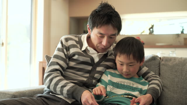 father and son using a digital tablet sitting on sofa - japanese ethnicity stock videos & royalty-free footage