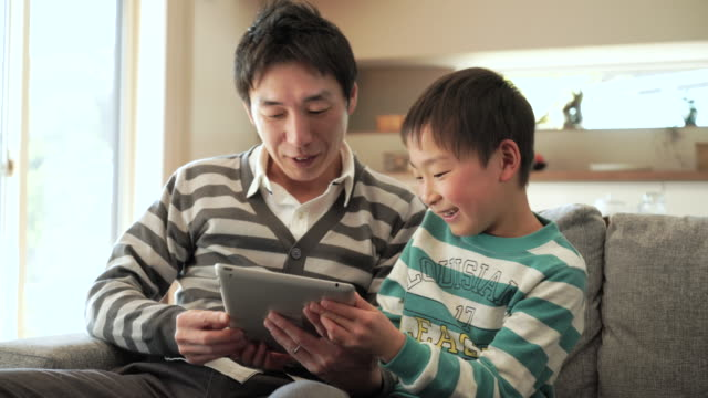 father and son using a digital tablet - single father stock videos & royalty-free footage