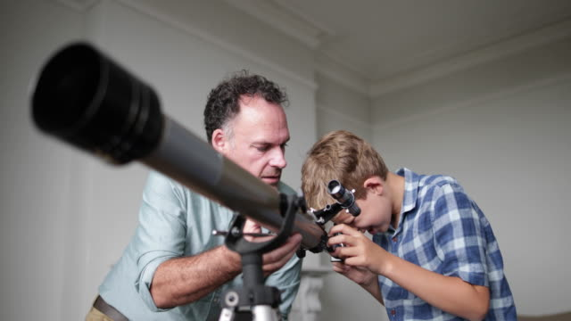 Father and Son using a telescope