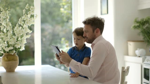 Father and son using digital tablet in domestic room.