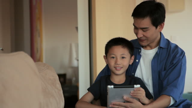 ms father and son using digital tablet together in living room / china - 6 7 jahre stock-videos und b-roll-filmmaterial