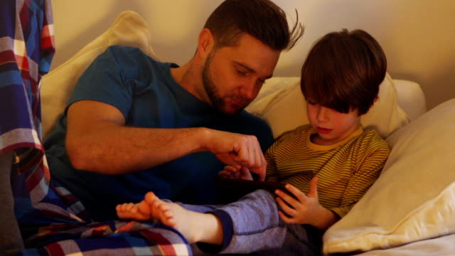 father and son using digital tablet - bedtime stock videos & royalty-free footage
