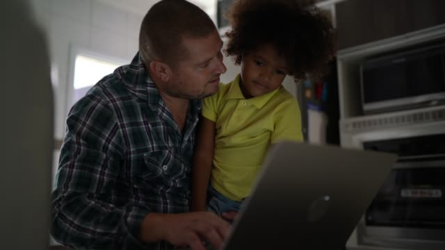 father and son using laptop at home - genderblend stock videos & royalty-free footage