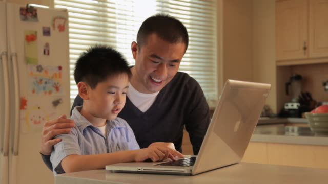 MS Father and son using laptop on kitchen counter / China
