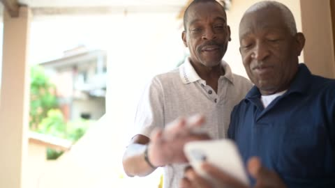 father and son using mobile phone at home - cell stock videos & royalty-free footage