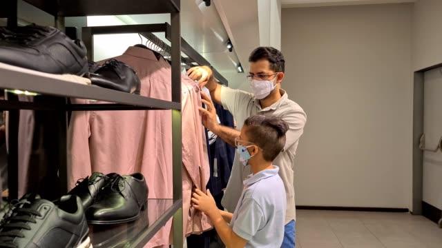 vídeos y material grabado en eventos de stock de padre e hijo usando la máscara n95 y comprando en la tienda de ropa - boutique