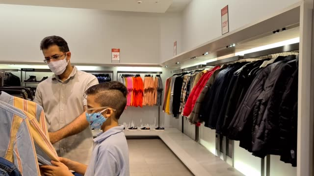 father and son using n95 mask and buying at the clothing store - clothes shop stock videos & royalty-free footage