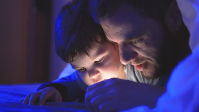 vater und sohn mit telefon vor dem schlafengehen - jungen stock-videos und b-roll-filmmaterial