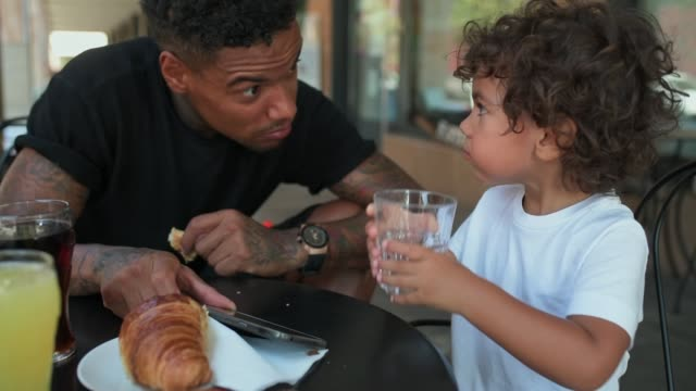 father and son using smart phone - croissant stock videos & royalty-free footage