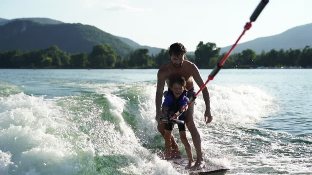 father and son wake surfing on alpine lake at sunset - 航跡点の映像素材/bロール