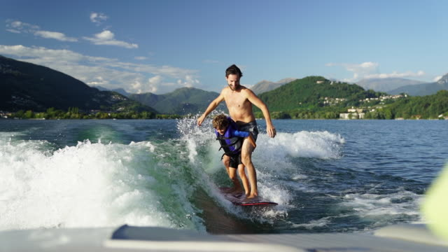 father and son wake surfing on lake at sunset, both fall in water - son stock videos & royalty-free footage