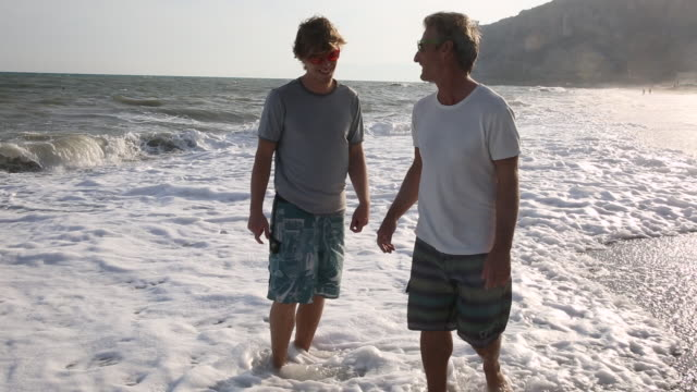 Father and son walk along beach, discussing
