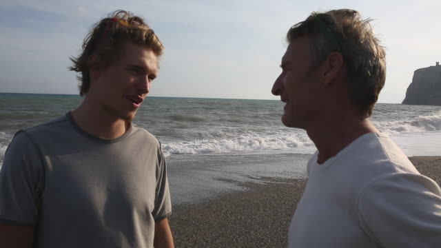 father and son walk along beach, discussing - son stock videos & royalty-free footage
