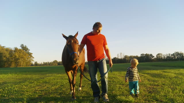 HD STEADY: Father And Son Walking A Horse