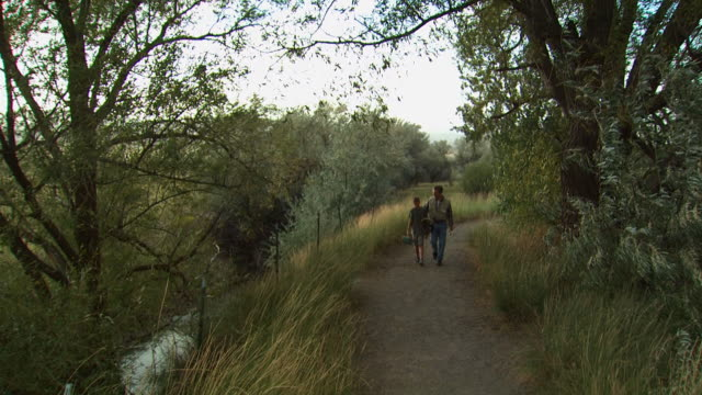 father and son walking down a trail - see other clips from this shoot 1171 stock videos and b-roll footage