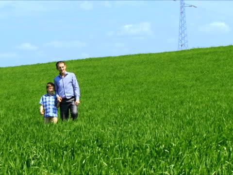 父と息子のフィールドを歩く - 談笑する点の映像素材/bロール