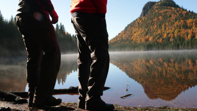 father and son walking on lake shore, autumn season - hunting stock videos & royalty-free footage