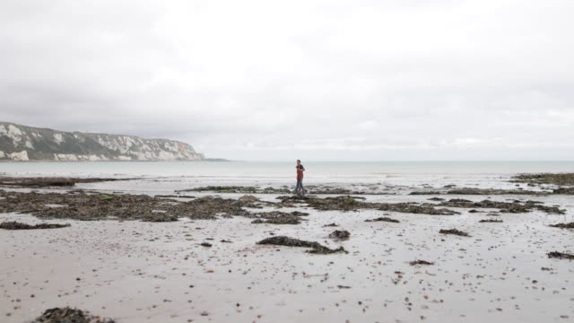 father and son walking on natural beach - kent england stock videos & royalty-free footage