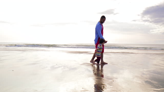 father and son walking on the beach - northumberland coast stock videos & royalty-free footage