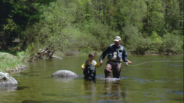 slo mo ws father and son (8-9) walking through river on fly fishing trip / maine, usa - maine stock videos & royalty-free footage