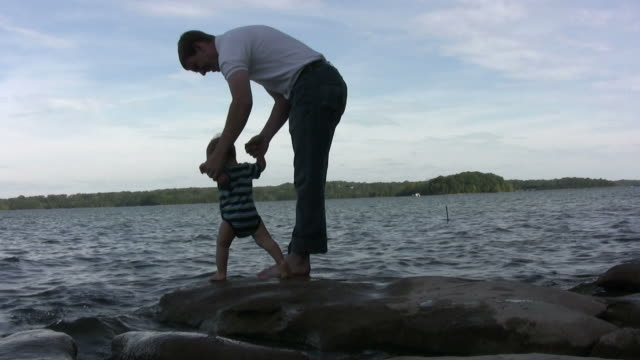 father and son walking to water - genderblend stock videos & royalty-free footage