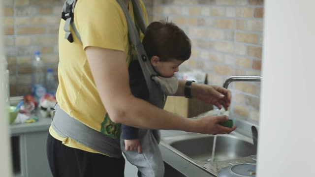 father and son washing dishes in kitchen sink - washing up stock videos and b-roll footage