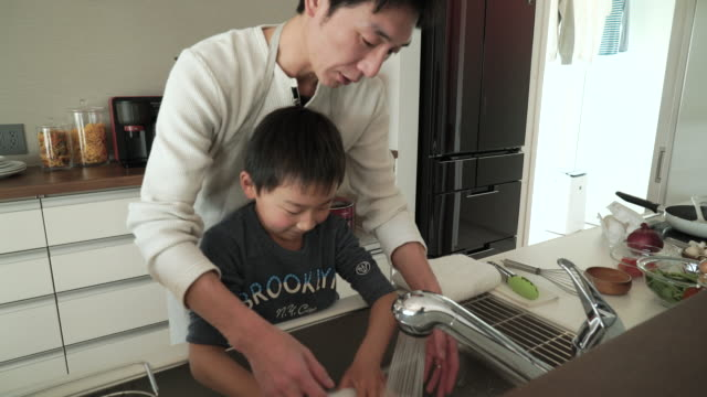 father and son washing the dishes together in the kitchen - only japanese stock videos & royalty-free footage