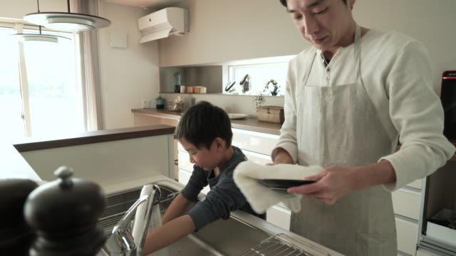 父と息子の洗濯しながら、キッチンでお料理を - 家事点の映像素材/bロール